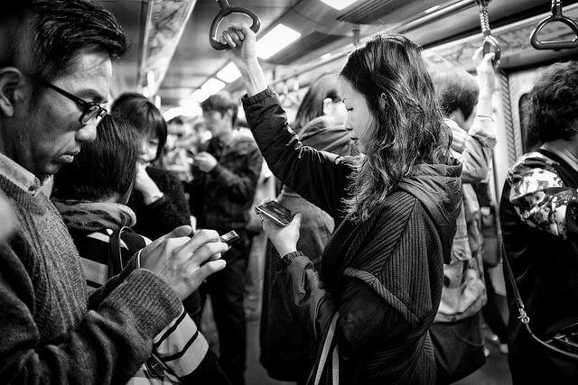mensen bekijken hun sociale media voor updates in de trein tijdens de spits