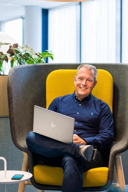 Han Strijbos from HEYDAY laughing at the camera while sitting on a remote workstation