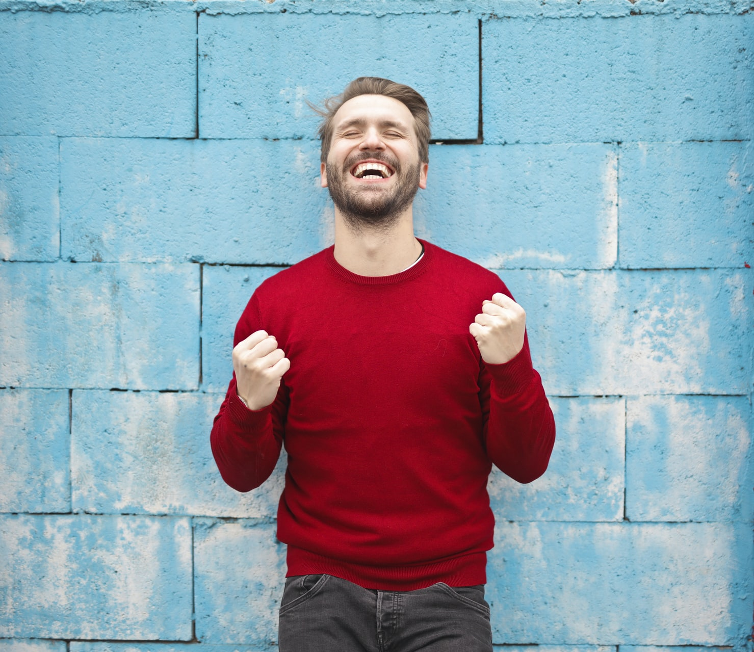 Man celebrating a victory in front of a blue wall
