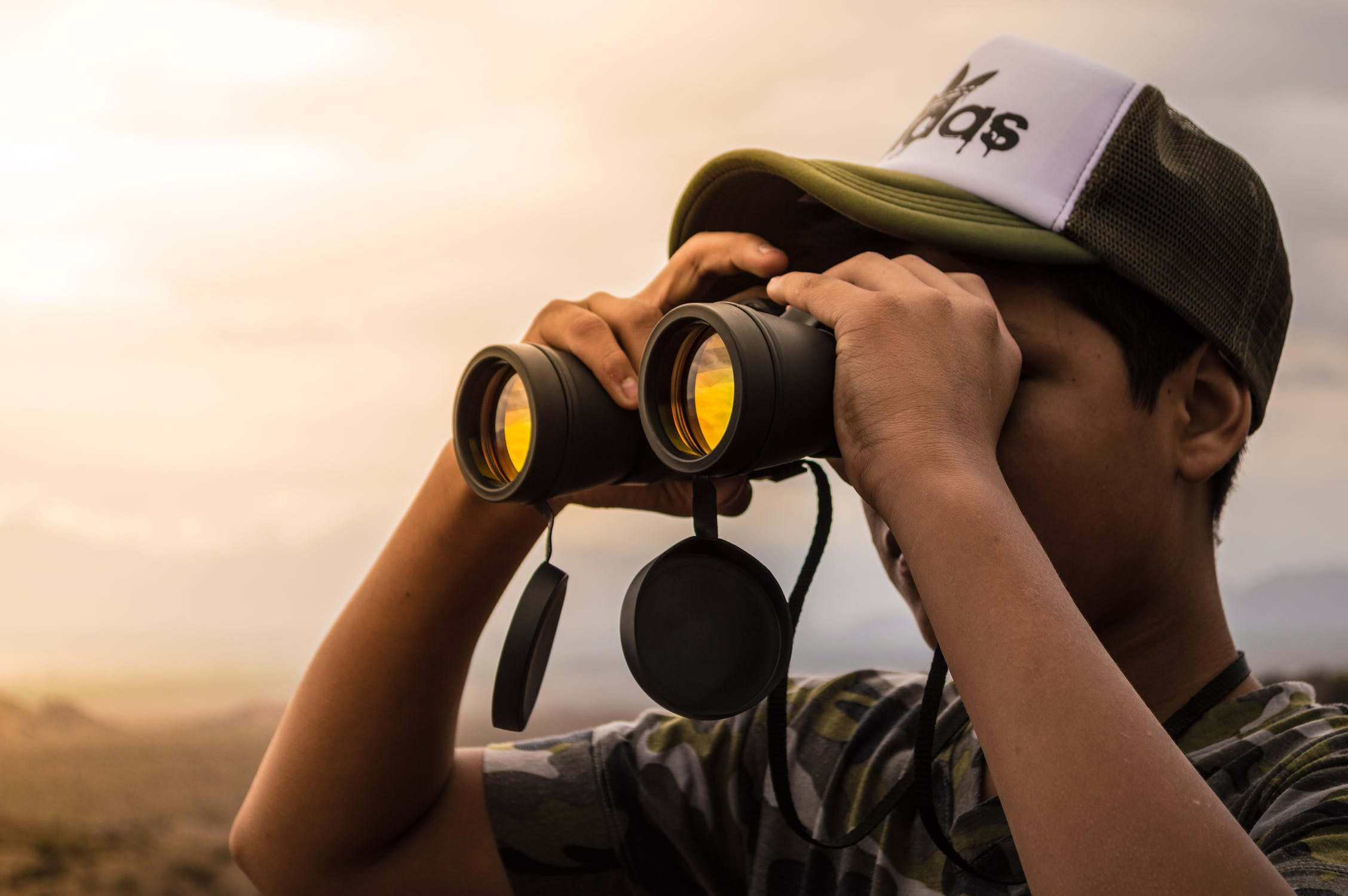 man using his binoculars to look in the distance