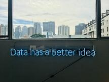 neon letters about data in front of a skyline