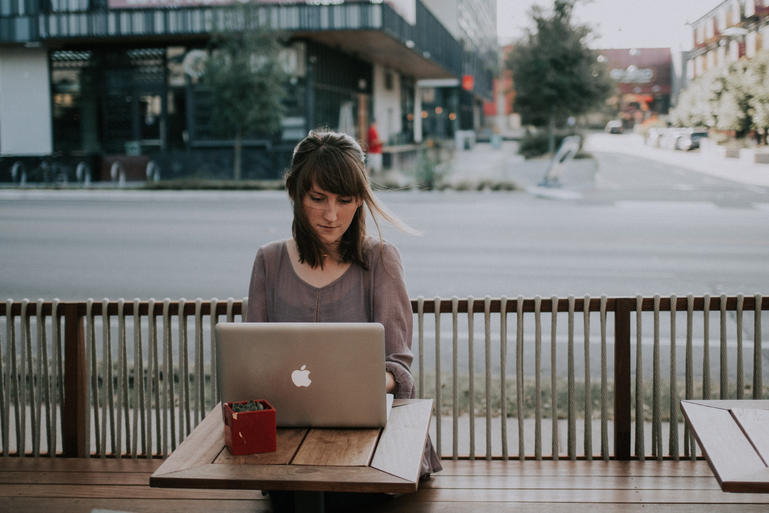 a woman who is working remotely on a macbook outside a coffeeshop